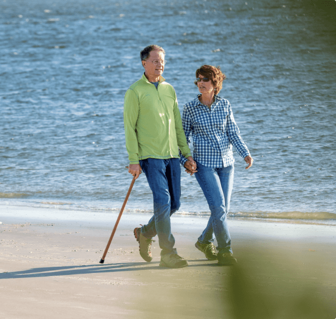 Man with a cane walking with his wife on the beach.