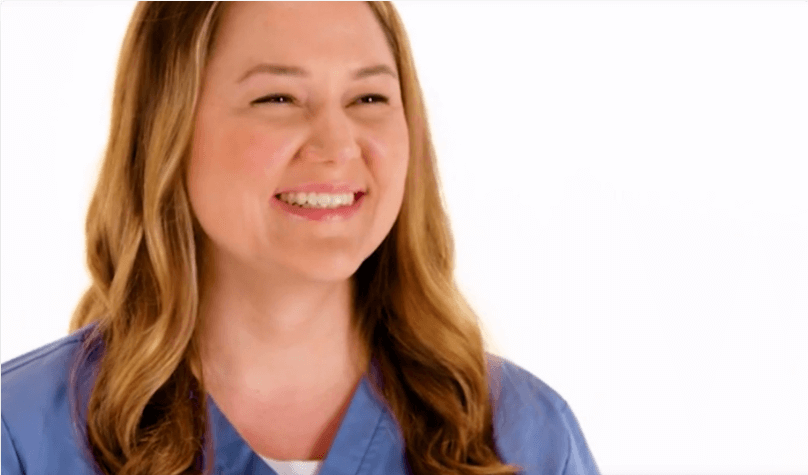 Woman in blue scrubs smiling.