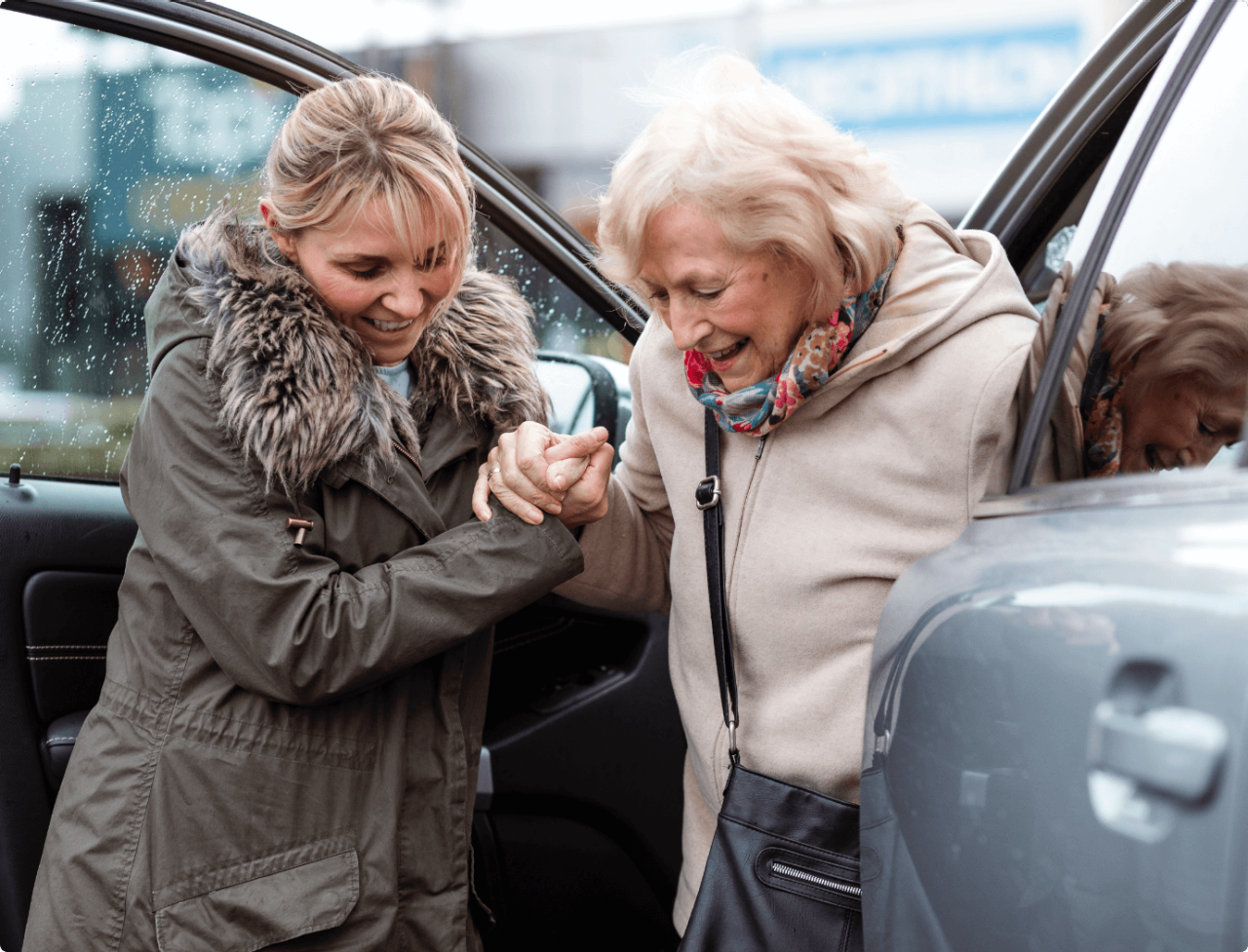 A woman helping another woman to get out of a car.