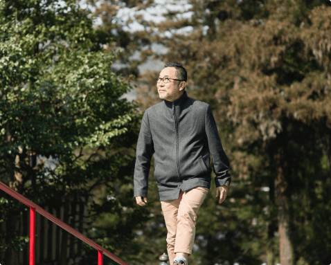 A man walking across a bridge in a wooded area.