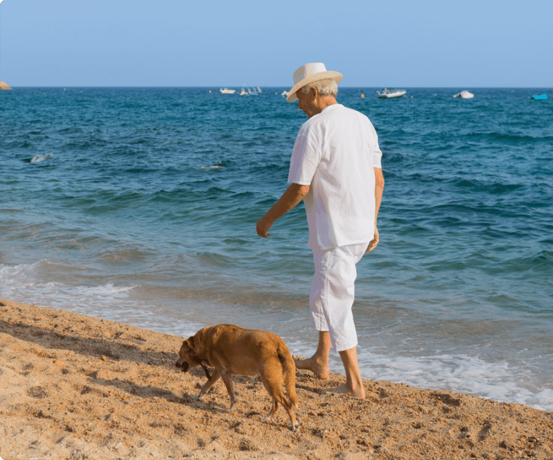 Spinal Cord Stimulation patient Paul walking his dog on the beach.