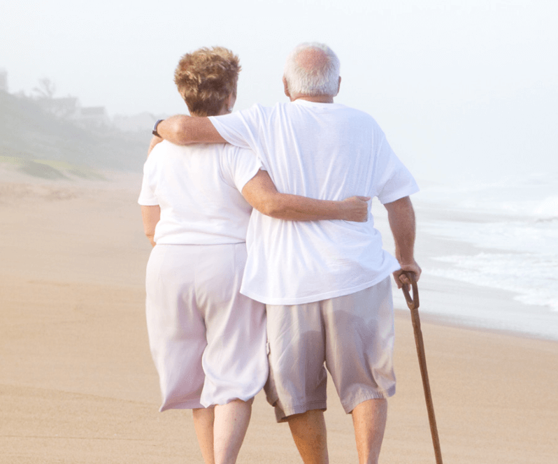 Spinal Cord Stimulation patient Deborah walking on the beach with her husband.