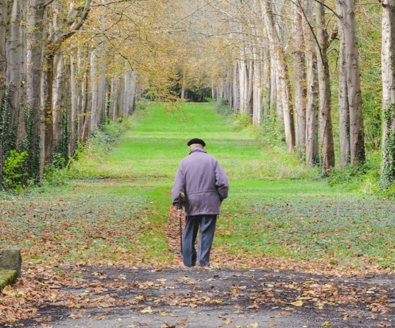Spinal Cord Stimulation patient Harold walking through a field.