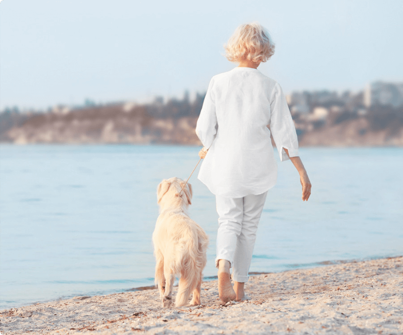 Spinal Cord Stimulation patient Roxanne walking her dog on the beach.