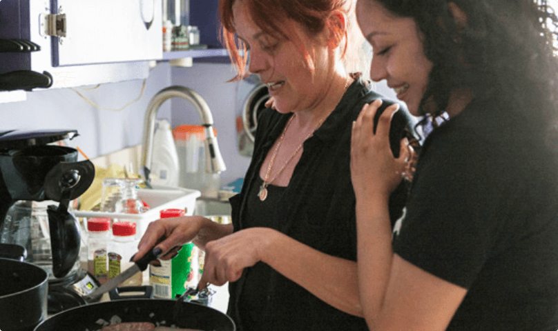 Two women cooking in a kitchen.
