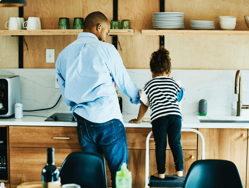 Father and daughter washing dishes in a kitchen sink.